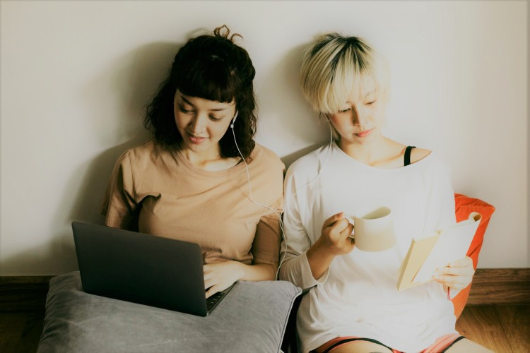 Two women listening to music on a laptop