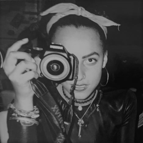 Black and white photo of Erin James holding a camera