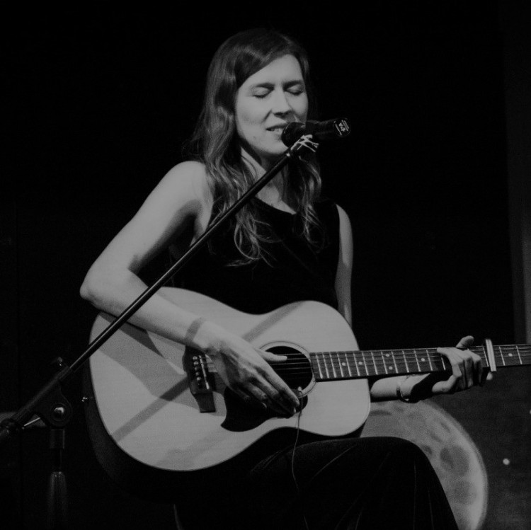 Black and white photo of Laura Lamn playing guitar and singing on stage
