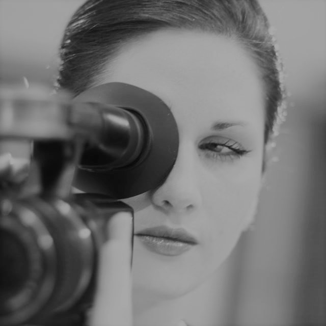 Black and white photo of Rona Walter holding a film camera